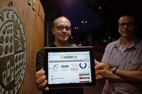 Uno de los dos creadores sostiene una tablet con su página web. | Manuel Cuevas
