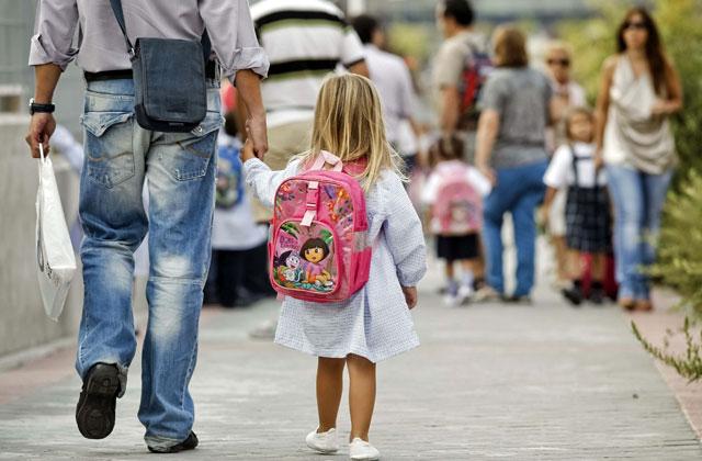 Una niña de la mano de su padre camino de clase al inicio del curso escolar, en el colegio de Madrid. | Efe