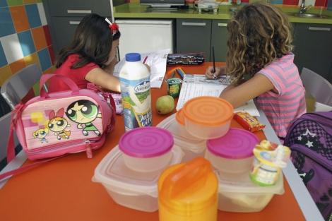 Dos niñas en una cocina con los tupper para el colegio. | Eugenio Torres
