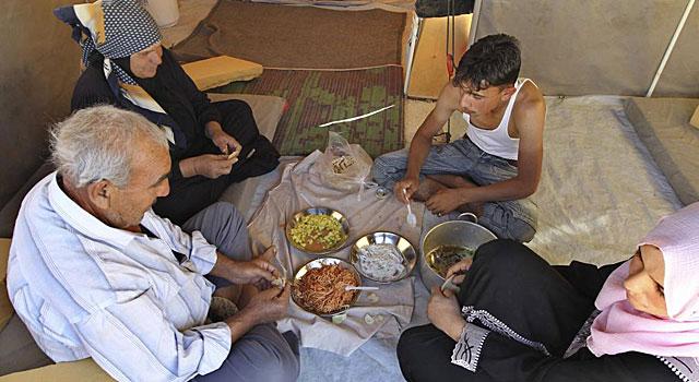 Una familia almuerza en el campamento de refugiados de Al Zaatri, en Jordania. | Reuters