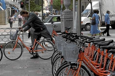 Un usuasrio coge una de las bicicletas del servicio municipal de préstamo.| E.M.