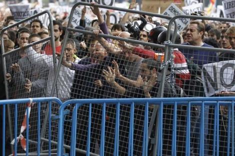 Manifestantes del 25-S tratando de derribar las vallas de protección. | Reuters