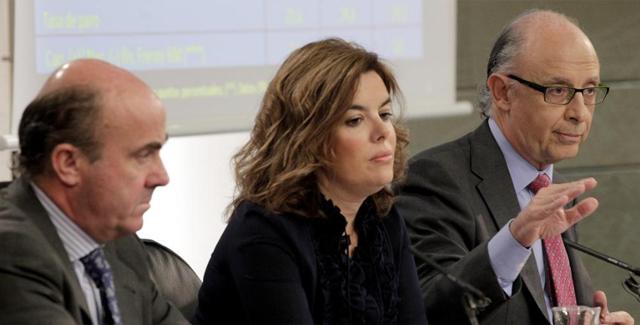 La vicepresidenta, Soraya Sáenz de Santamaría, y los ministros Cristóbal Montoro (d) y Luis de Guindos. | Efe