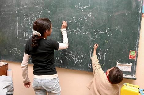 Dos niños procedentes de Marruecos escriben en la pizarra de una clase en Valladolid. | E.M.
