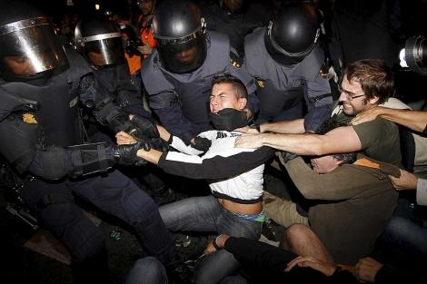 Varios agentes de la Policía forcejean con manifestantes del 25-S. | Chema Moya / Efe