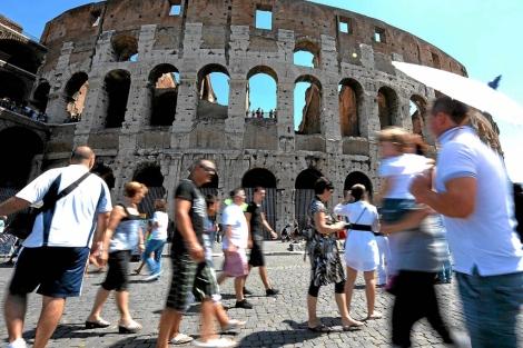 Varios turistas, en el Coliseo romano. | Efe