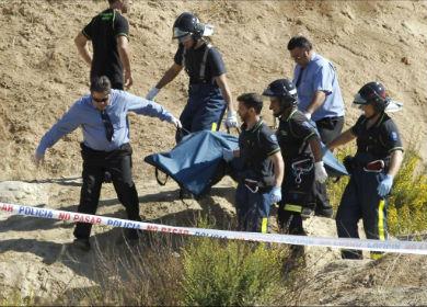 Un grupo de bomberos trasladan el cuerpo del menor.| Efe