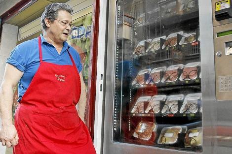 El propietario de la carnicería frente a la máquina expendedora. | R. PÉREZ