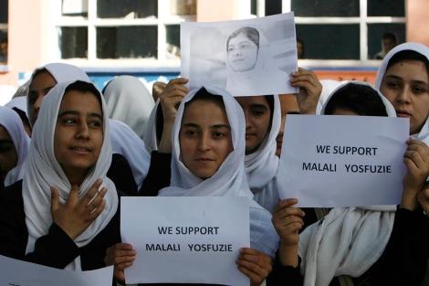 Una estudiante sostiene una fotografía de Malala mientras reza por su recuperación. | Efe
