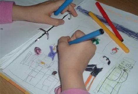 Una niña colorea una de sus figuras.