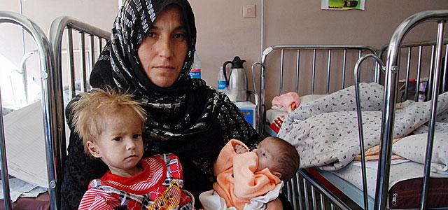 Sima Gul, con sus dos niñas malnutridas, este martes en el hospital de Kabul.| M. Bèrnabé