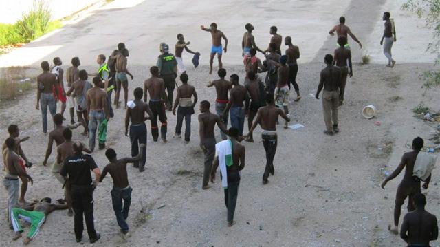 Decenas de subsaharianos tratan de saltar la valla de Melilla.   Efe