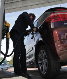 Una mujer llena el depósito en una gasolinera. | Paco Toledo