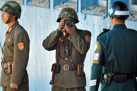 Un soldado norcoreano hace una fotografía a otro surcoreano en la frontera.   Afp