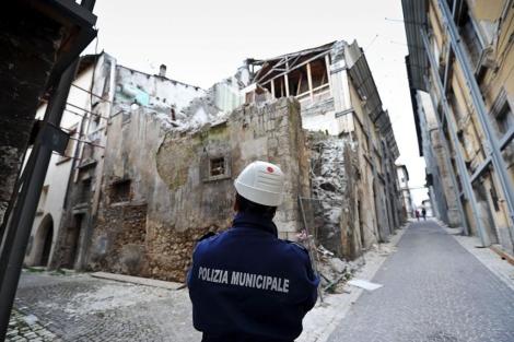 Un policía contempla las ruinas de edificios en la zona roja cerrada desde hace tres años.| Afp