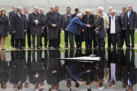 Merkel observa cómo un superviviente le da la mano al arquitecto del monumento. | Reuters