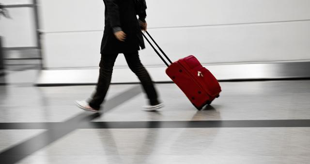 Una joven arrastra su maleta en un aeropuerto.   E.M.
