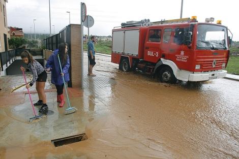 Vecinos intentan evitar la entrada del agua en sus viviendas en Córdoba. | M. Cubero