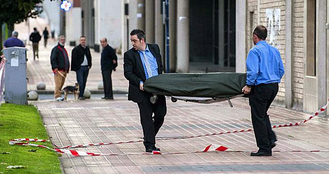 Trabajadores de la funeraria trasladan el cadáver de la fallecida. | Efe