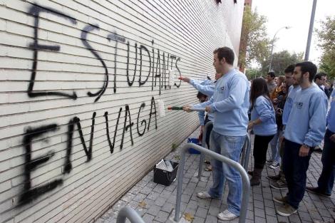 Los estudiantes de Unió d'Estudiants Valencians borran las pintadas. | José Cuéllar
