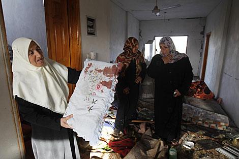Mujeres palestinas inspeccionan su casa al norte de la Franja de Gaza. | Afp