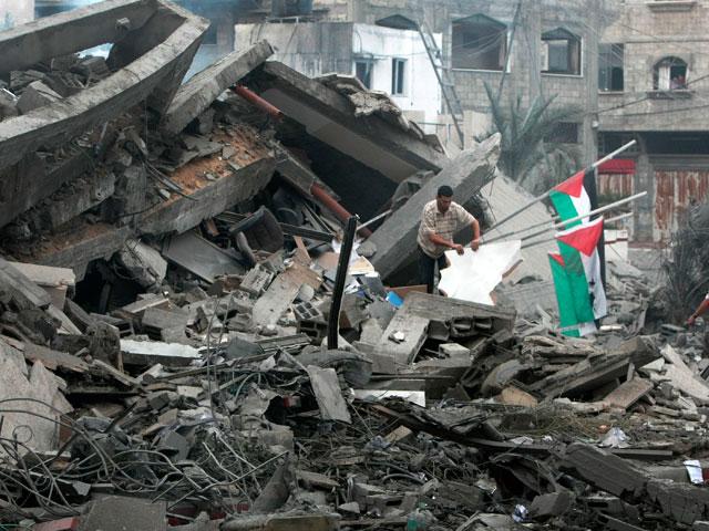 Dos palestinos inspeccionan la sede del primer ministro de Hamas en Gaza. | Afp