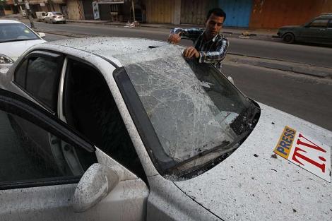 Un periodista palestino inspecciona su coche, atacado en Gaza. | Afp