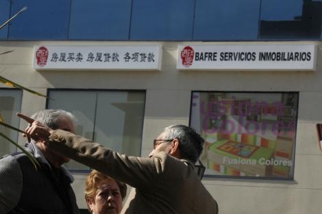 Unas personas frente a una inmobiliaria con un letrero en chino en Usera, Madrid. | A. X.