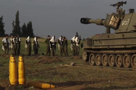 Soldados israelíes rezan junto a proyectiles y tanques en la frontera con de Gaza. | Efe