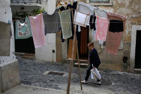 Una mujer pasa delante de ropa tendida en el barrio de Alfama. | Reuters