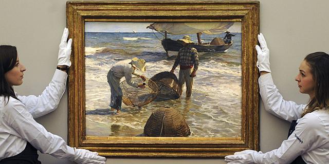 Dos empleadas de Sotheby's preparando la obra de Sorolla 'Pescadores valencianos'. | Efe