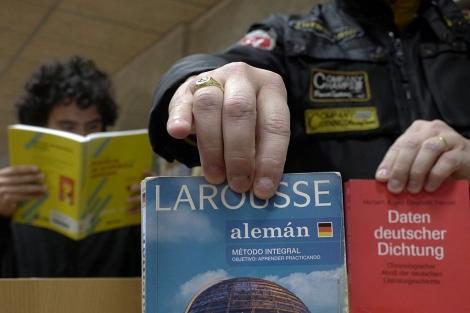 Un joven muestra diccionarios y guías de alemán. | M. Cuevas