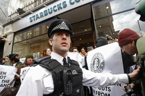 Un policía vigila a los manifestantes a la puertas del Starbucks de Londres. | Reuters