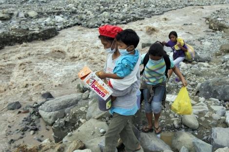 Residentes de New Bataan caminan por la ciudad provistos de mascarillas. | Epa