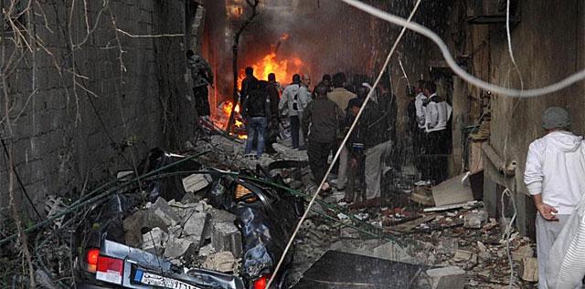 Un grupo de personas inspecciona los daños causados tras la explosión del un coche bomba en Damasco. | Afp