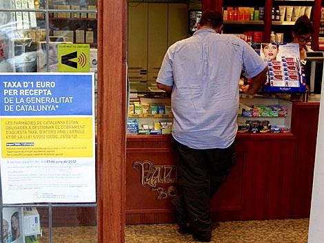 Farmacia catalana con el cartel que avisa del cobro de la tasa. | Domènec Umbert
