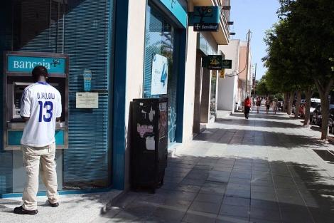 Un inmigrante saca dinero de un cajero automático en El Ejido. | M. C.