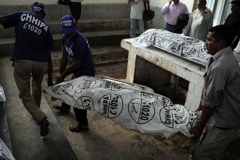 Trabajadores trasladan los cadáveres de vacunadores asesinados en Karachi. | Afp