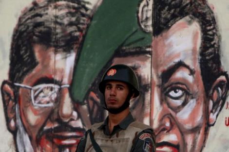 Un miembro de la Guardia Republicana delante de dos caricaturas de Mursi y Mubarak. | Reuters