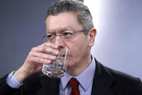 El ministro de Justicia bebe agua durante una rueda de prensa.   Efe