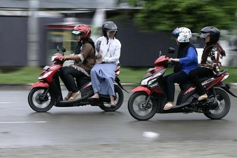 Varias mujeres, en moto en Banda Aceh.| Reuters