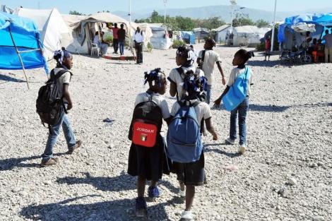 Un grupo de niños pasa por un campamento de camino a clase en Marassa,   Reuters
