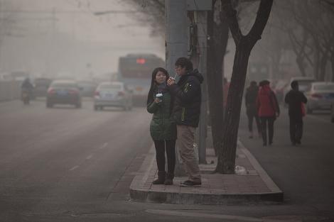 Dos jóvenes toman un refresco en una calle de Pekín afectada por la polución. | Afp