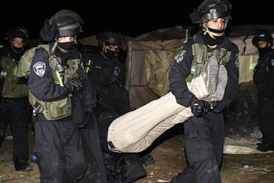 Agentes israelís desalojando a uno de los activistas del campamento. | Reuters