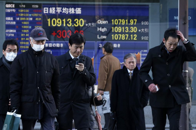 Varios hombres caminan junto a un panel que muestra el índice Nikkei.   Efe