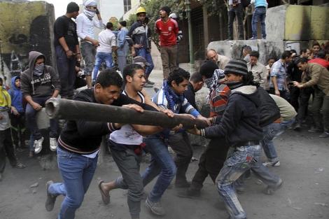 Manifestantes egipcios tratan de destruir el muro que separa el complejo gubernamental. | Efe