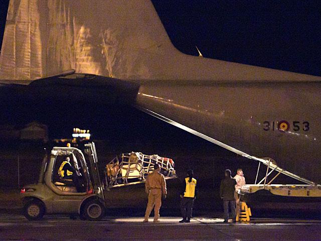 Efectivos militares cargan el 'Hércules' C-130 antes de despegar en la base aérea de Zaragoza. | Foto: Efe / Javier Cebollada.
