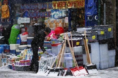 Un hombre limpia la nieve en una tienda en Buxton. | Reuters