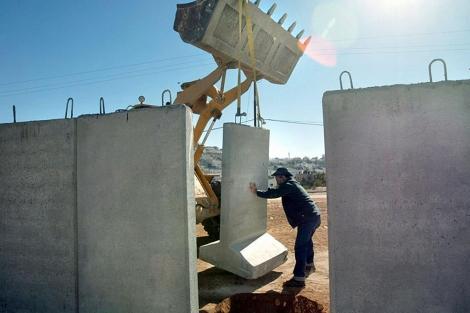Colocación de un muro de protección en un asentamiento en Hebrón, Cisjordania.