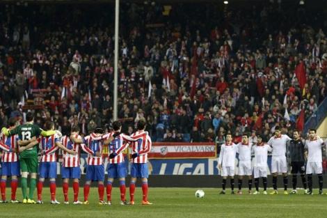 Atlético y Sevilla, ayer, en el minuto de silencio que se guardó antes del partido.   Efe